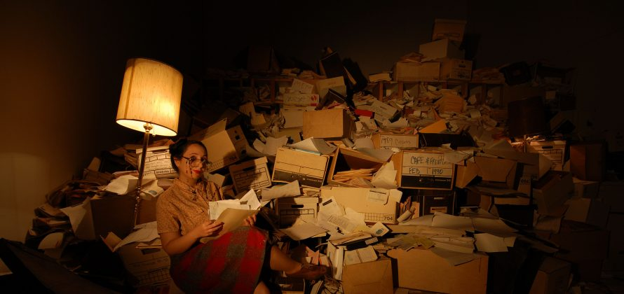 Performer Ayne Terceira is dressed as a librarian might be, with legs crossed sitting beside a floor lamp. She appears to be viewing a file folder with many pages inside and is set against an enormous pile of bankers boxes, loose papers, and administrative paperwork in the background.