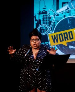 a woman is animatingly telling her story on the wordplay stage